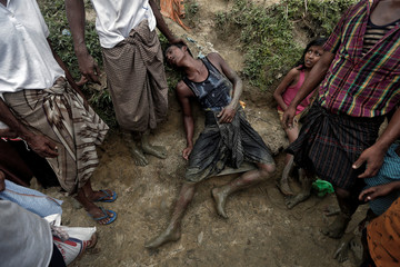 A Rohingya refugee collapses while waiting to receive aid in Cox's Bazar, Bangladesh