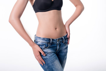Young woman in jeans with beautiful flat belly.