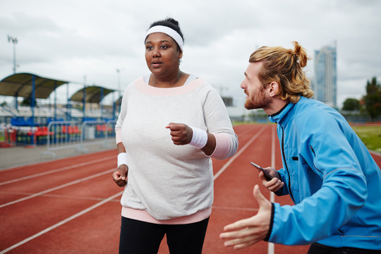 Professional trainer encouraging young chubby woman to run faster before finish
