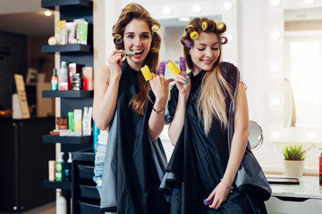 Young pretty girls in capes with hair curlers goofing around in beauty salon. Girlfriends showing devil horn and piece gesture with rollers on fingers having fun together