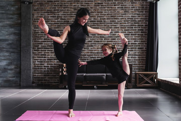 Cute little child girl and adult woman doing standing split balance gymnastic exercise in a living room