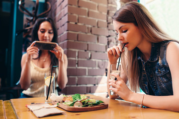 Two girlfriends having healthy lunch in cafe. Young woman taking picture of food with smartphone posting on social media