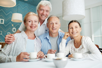 Company of affectionate senior friends spending time in cafe at leisure