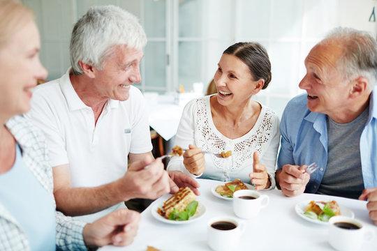 Cheerful senior friends having tasty dessert and talking in cafe