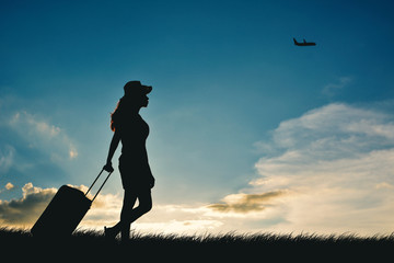Silhouette of women travel walking with luggage at the sky sunset