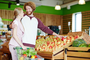 Amorous young couple choosing fresh apples in supermarket