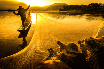 Photographers soak in water while taking pictures of fisherman in Thailand.