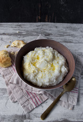 Southern grits with bisquit and butter in rustic setting