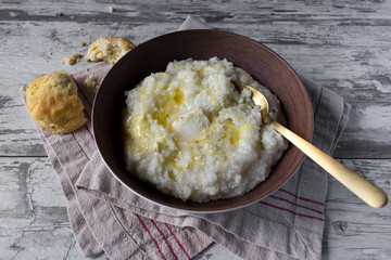 Southern grits with bisquit and butter in rustic setting with spoon
