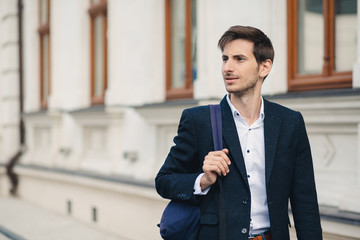 Portrait of young man with backpack in the city