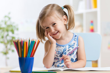 Cute little girl drawing with colorful pencils on paper. Pretty child painting indoors at home, daycare or kindergarten