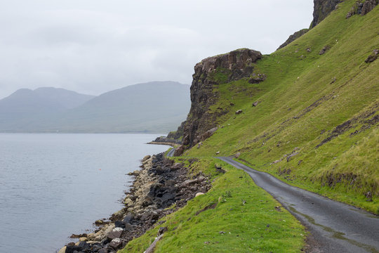 Seafront road below a Scottish cliff under the rain