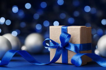Gift box or present and christmas balls against blue bokeh background. Magic holiday greeting card.