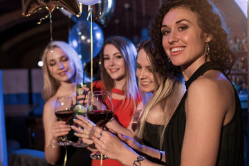 Cheerful girls clinking glasses of wine at the party in night club