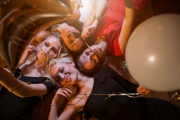 Low angle view of four beautiful Caucasian women fooling around making fake moustache from their own hair lying on table in cafe,