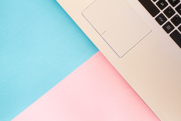 Top view of laptop notebook on blue and pink color background