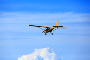 Samolot awionetka ultralekki w powietrzu na błękitnym niebie.