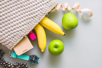 woman diet healthy active lifestyle Concept, fruit eating dieting concept - bananas, apples, smart phone, cosmetics, watch, accessories in bag. Top view, close up. copy space for text.