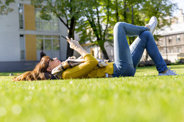 Young woman using her smart phone while laying on grass in park on her lunch break