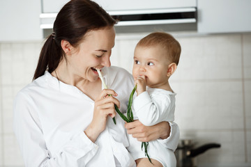 Funny portrait of young beautiful mother looking at her little boy while he looking at her with curious expression. They eating green onion at kitchen.