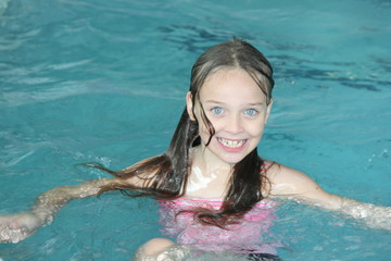 Young girl-child, playing in and, having fun in a swimming pool.