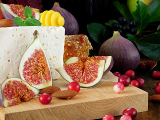 Cheese made of sheep milk and slices of figs on a wooden board surrounded by cranberries and almond. Ingredients for a cheese plate