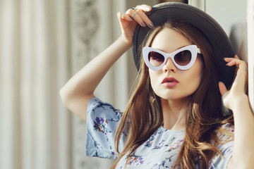 Outdoor close up portrait of young beautiful fashionable woman posing in street. Model wearing stylish gray boater hat, retro white sunglasses. Female fashion concept. Copy, empty space for text Wall mural