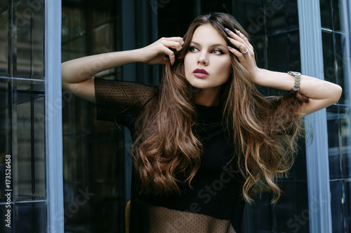 6f3651f14a7 Outdoor waist up portrait of young beautiful girl with long curly hair  posing in street