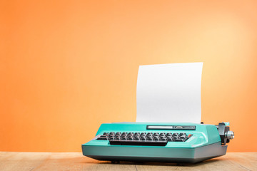 Retro old mint green typewriter with paper sheet on wooden desk front orange wall background. Vintage instagram style filtered photo