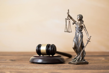 Themis statue and gavel on wooden table