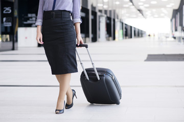 Business woman walking with wheeled bag