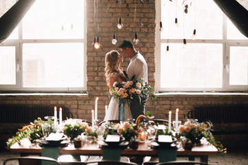 beautiful bride and groom in room with decorated table with flowers, candles and light bulbs