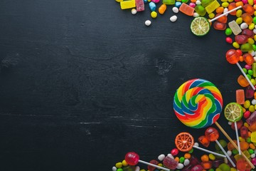 Colored candies, sweets and lollipops. On a black wooden background. Top view. Free space.