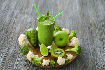 Healthy smoothie with kale in glass on wooden board