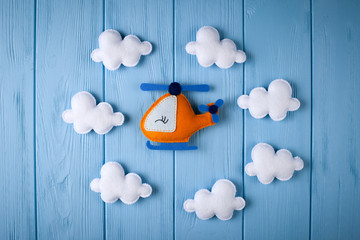 Orange craft helicopter and clouds on blue wooden background with copyspace. Felt handmade toys. Empty space for text. Top view.