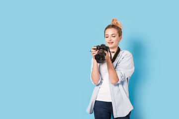 Young blonde photographer holds a camera and looks at the photo she made