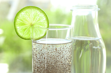 Chia seeds in glass of water on blurred background