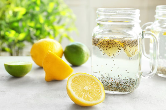 Mason jar with chia seeds, lemon and water on kitchen table