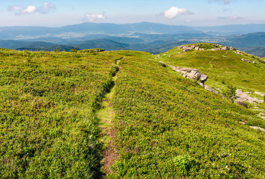 path through grassy meadow to huge boulders