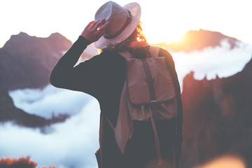 Spoed Foto op Canvas Alpinisme Young traveler woman wearing backpack and hat standing on edge of cliff and enjoying landscape, sunset, mountains and clouds.