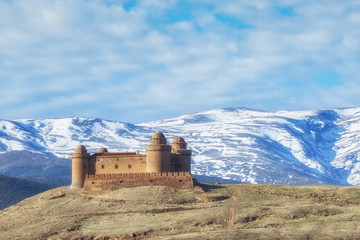 Castle Calahorra with the snow capped mountains of the Sierra Nevada, Granada Province, Andalusia, Spain.