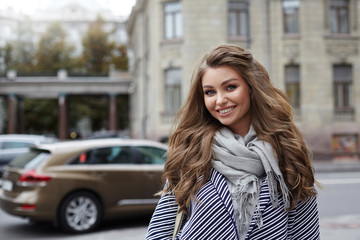 Beautiful cheerful young lady with voluminous hair wearing stylish coat and scarf posing on city street on her way to store, having joyful happy look, enjoying warm spring day. People and lifestyle