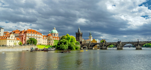 Landscape of the romantic city of Prague under a blue sky. Panoramic view of Charles bridge and old town on a summer day in the capital Czech Republic. Cruise on the Moldovan river.