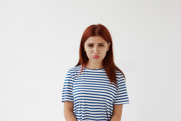 Horizontal studio portrait of upset sad Caucasian teenage girl with red colored hair and pursed lips having disappointed unhappy look, frowning and pouting after quarrel or fight with her boyfriend