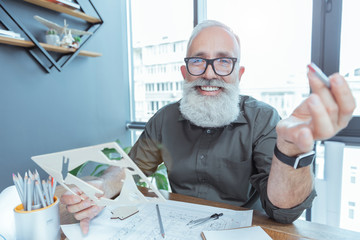 Positive gray-haired architect is holding pattern with smile