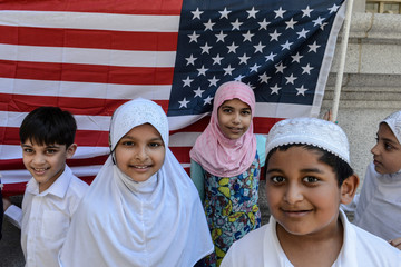 Children pose for a photograph in front of an American flag during the annual Muslim Day Parade in New York City