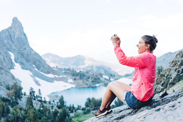 Young brave woman sitting high in mountains and taking photo using her phone. Risky rock climbing in peaceful wilderness area. Enjoying amazing snowy lake view