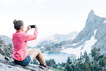Young brave woman sitting high in mountains and taking photo using her smartphone. Risky rock climbing in peaceful wilderness area. Enjoying amazing snowy lake view