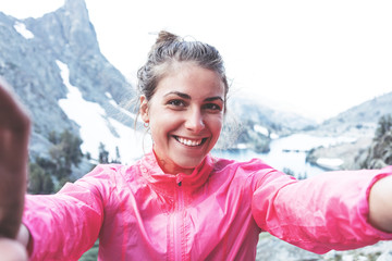 Cheerful young woman taking self portrait photo high in mountains. Risky rock climbing in peaceful wilderness area. Enjoying amazing snowy lake view