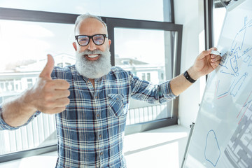 Positive old male in glasses is expressing happiness